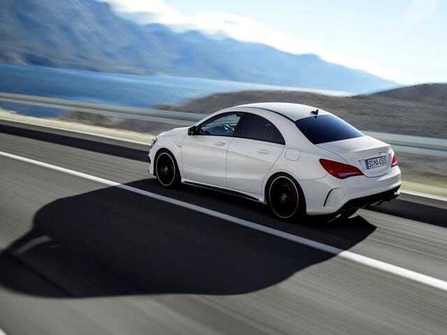 Белый автомобиль едет по дороге
